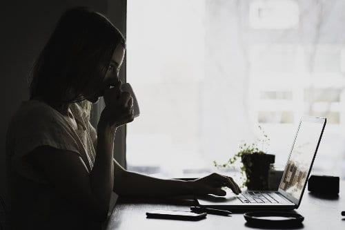 Kobieta siedzi przy komputerze i pije kawę