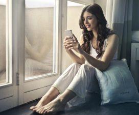 Kobieta siedzi przy oknie z telefonem komórkowym