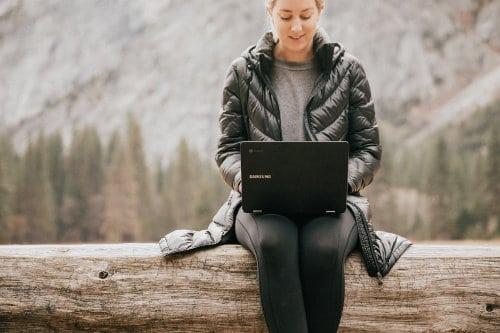 Kobieta siedzi na pniu drzewa z laptopem na kolanach