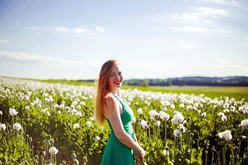 Kobiteta w zielonej sukience stoi wśród kwiatów