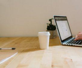 Kubek papierowy stoi obok laptopa