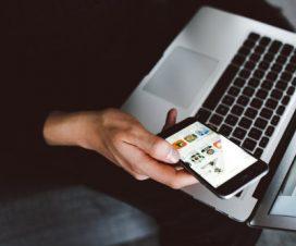 Mężczyzna sprawdza telefon komórkowy siedząc przy laptopie