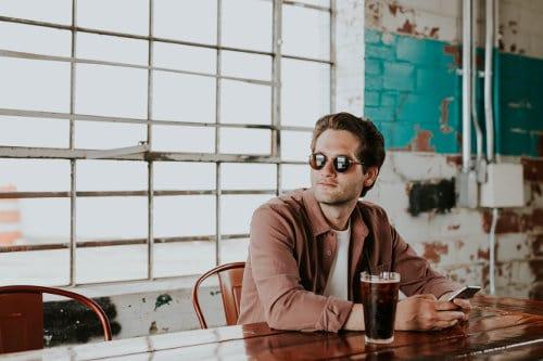 Mężczyzna siedzi w barze i trzyma telefon komórkowy