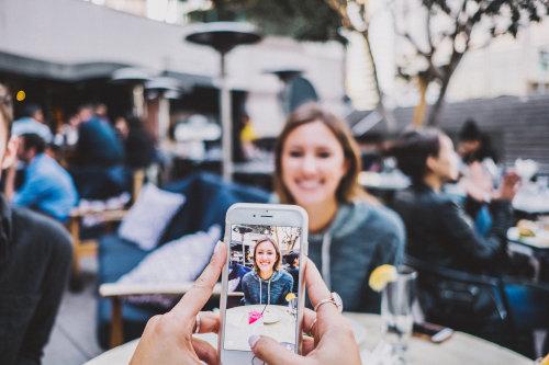 Mężczyzna robi zdjęcie kobiecie telefonem komórkowym